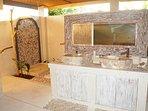 Pavilion Sumba has a terrazo bathtub a Marble Shower with Petrified Wood stone, and Onyx Sinks