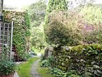Mossy cobbled lane from front door of cottage towards stream