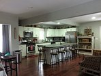 -108' island that seats 10 in a modern kitchen with every utensil that you would need