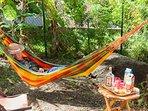 à l'ombre du palmier Phoenix sieste ou apéro, le rêve ! Hamac et chaises longues.