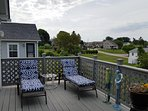 Exit the upstairs Living Room to a deck with dining area, lounge chairs & grill.