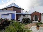 Location indépendante. Terrasse couverte couleur blanche et porte coulissante bleue