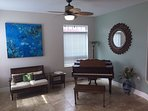 Opposite side of the living room with original art and grand piano