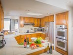 Cook in a kitchen with a view!  With gas stovetop, double oven, microwave,  and well stocked kitchen