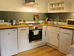 Kitchen with gas hob, electric fan oven, dishwasher, microwave