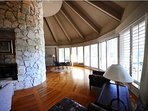 Large, lovely living room with 2 story oval white coral chimney, and view of lagoon.