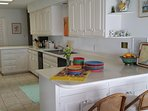 Bright, airy, and fully stocked, updated kitchen with views of the bay