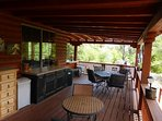 Large covered deck off living room with built in grill for entertaining. View of 14 acres of boulder