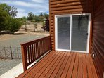 Small back deck with small fenced yard and doggie door.