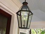 Locally-made Bevolo gaslight gently illuminates the porch with a soft, traditional glow