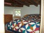 Schlafbereich mit Doppelbett im oberen Bereich der Maisonette Wohnung