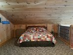 Loft bedroom with quilt, pine siding and deep memory foam king bed