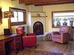 Gas log kiva fireplace in corner of living room. Quick heat!