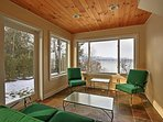 The enclosed sunroom has ample seating to enjoy views of the lake.