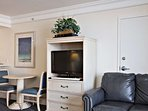 Living area features a flat screen television with satellite TV and DVD player and a table top for two.