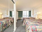 Large one bedroom suite features 2 queen size beds, large mirror door closet, dresser drawers, sitting chair and a flat...
