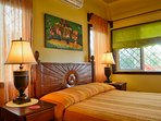 Master Bedroom accenting local Carving and Art. Great Reading lamps.