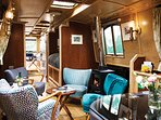 Narrowboat Grouse: Lounge with comfy chairs and log-effect gas stove.