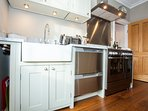 Butler sink, 2 drawer top-loading dishwasher and gas range cooker.