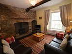 The Snug - a bright but cosy room with original features including beams, wood floors & fireplace