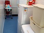 Utility room with fridge and washing machine.