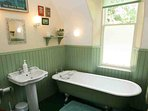 The first floor family bathroom is a bright and spacious room, with traditional suite and roll top bath