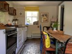 The characterful farmhouse kitchen with cobbled floor, butler sink and stable door view of courtyard