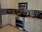 Fully equipped kitchen with 5-burner cooktop and double oven.