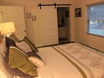 Master bedroom with queen bed and barn doors leading to bathroom and closet.