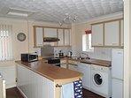 Kitchen area with microwave, oven, dishwasher, fridge freezer and washing machine.