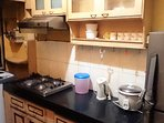 Kitchen with refrigerator, washing machine, gas burner, microwave oven, tea / coffee maker