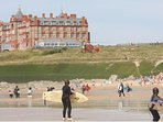 Fistral Beach and teh headland hotel with seating offering cream teas etc