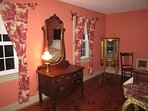 French toile drapes with forged iron hardware add to the ambience of this romantic room.