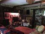 Cosy beamed sitting room, with large traditional Franklin Stove as an open fire + books & games