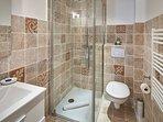 Modernised bathroom with walk-in shower, toilet, vanity unit.