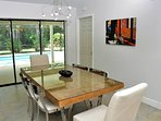 Dining area with sliding door wall towards covered patio & swimming pool