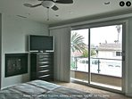 Master bedroom with fireplace, fan, sound system, big screen flat TV, ocean view,