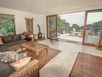 Lounge with log burner, patio doors opening onto deck with sea views