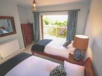 Twin bedroom, patio doors leading to deck overlooking the sea and woods