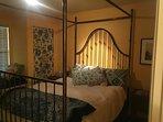 Bedroom features queen bed with luxurious down bedding, TV, dresser, desk, fridge, microwave & more