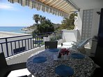 Large south facing terrace with bay view, dining table, sun loungers, wind-out awning.