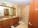 Ensuite second master bathroom with double sinks and large glass block/ travertine shower