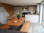 A bespoke oak dining table provides a convivial dining area for larger groups