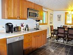 kitchen with dishwasher and ceramic glass cooktop, microwave, Kurrig coffee maker, toaster.