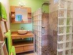 La salle d'eau attenante, comprend vasque, douche à l'italienne et WC