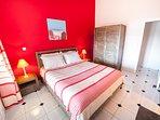 La chambre rouge, s'ouvre sur la terrasse par une porte vitrée, est chaleureuse et accueillante