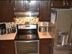 Kitchen with stainless steel appliances, coffee maker.