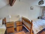 The second small bedroom has two single beds, one under the sloping ceiling