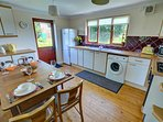 Good-sized kitchen including a washing machine and fridge/freezer and with dining table and chairs