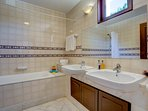 Spacious bathroom with bath and shower over bath and heated towel rack